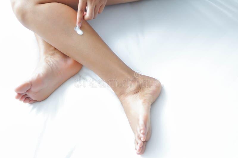 Рука женщины прикладывая сливк или лосьон на ноге лежа на белой кровати, выборочном фокусе стоковое фото