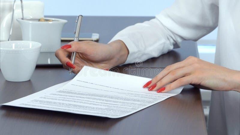 Рука женщины при красные ногти подписывая контракт стоковое фото