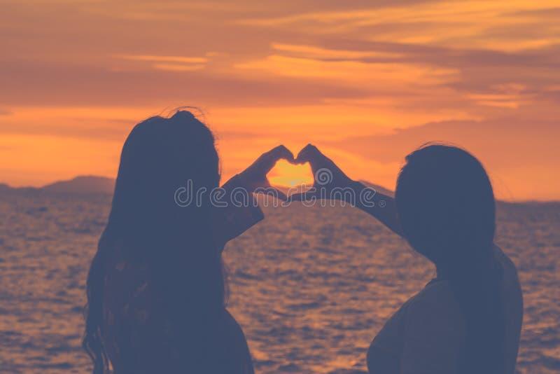 Рука женщины силуэта делает в форме сердц символ на заходе солнца на пляже стоковое изображение rf