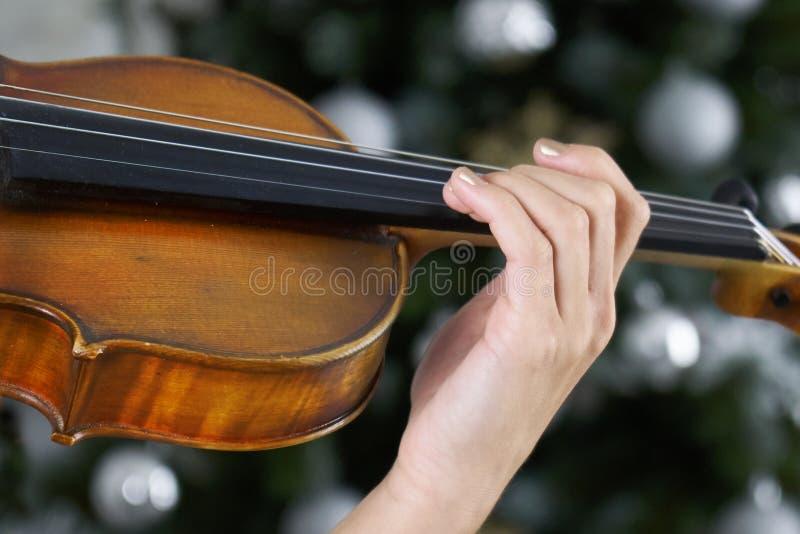 Рука женщины-скрипачи на доске с скрипкой с рождественской елкой стоковое изображение