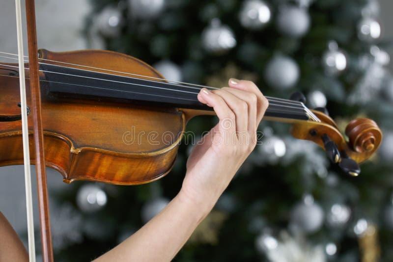 Рука женщины-скрипачи на доске с скрипкой с рождественской елкой стоковые изображения