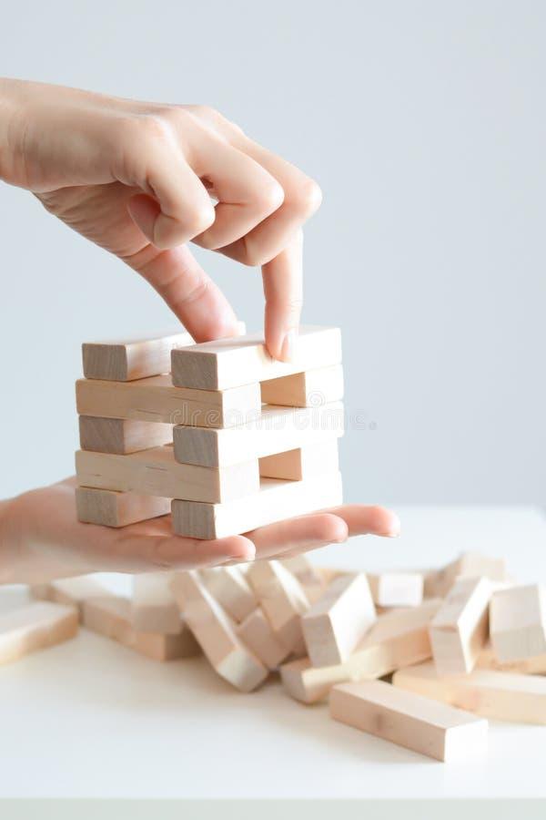 Рука женщины строя башню деревянных блоков на белой предпосылке стоковое фото