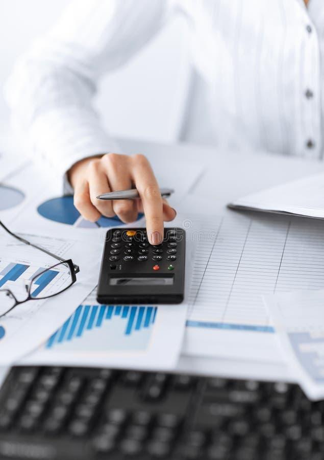 Рука женщины с калькулятором и бумагами стоковая фотография rf