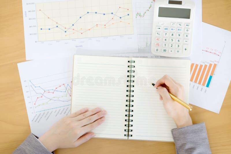Рука женщины с калькулятором и бумагами стоковое изображение
