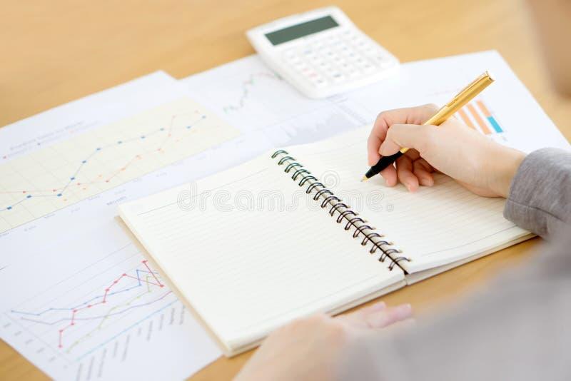 Рука женщины с калькулятором и бумагами стоковое фото rf