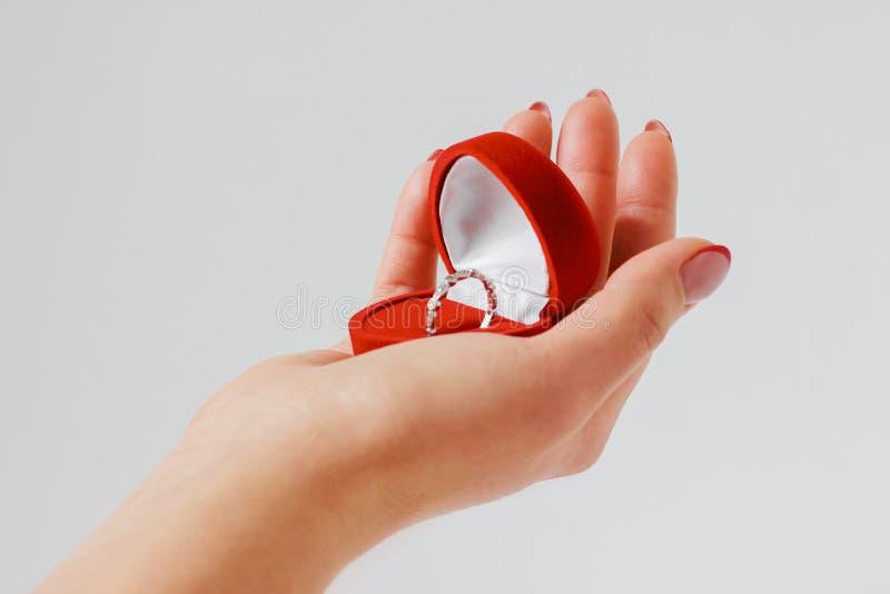 Рука женщины с обручальным кольцом в красной коробке на серой предпосылке стоковое фото rf