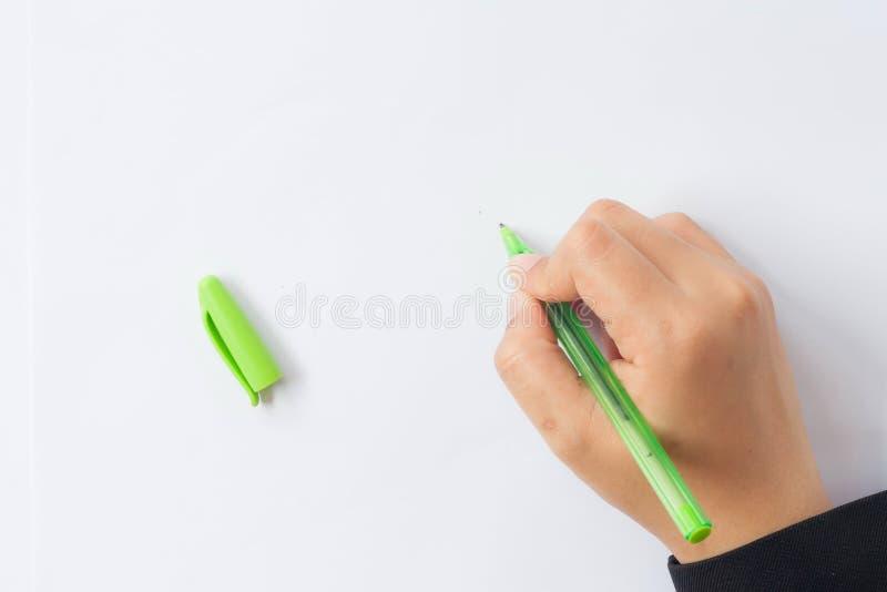 Рука женщины с ручкой на белой предпосылке стоковая фотография rf