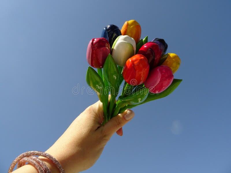 Рука задерживая букет красочного деревянного agaist тюльпанов предпосылка голубого неба стоковые фотографии rf