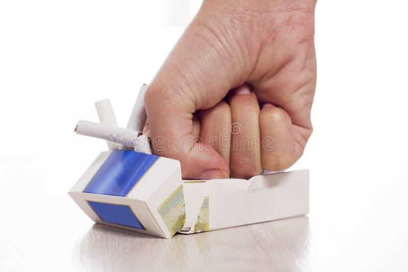 Рука задавливая сигареты стоковое изображение