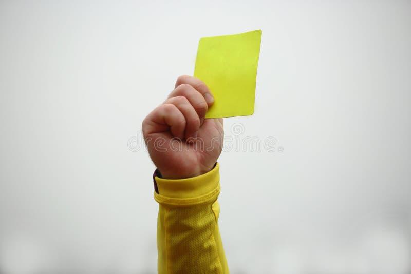 Рука задерживая желтую карточку стоковая фотография