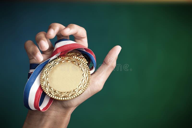Рука задерживая золотую медаль стоковые изображения