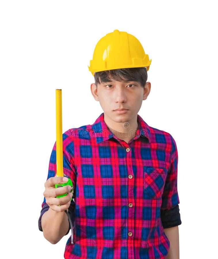 Рука инженера держит рулетку в его руках и носит желтую пластмассу шлема безопасности на белой предпосылке стоковое фото