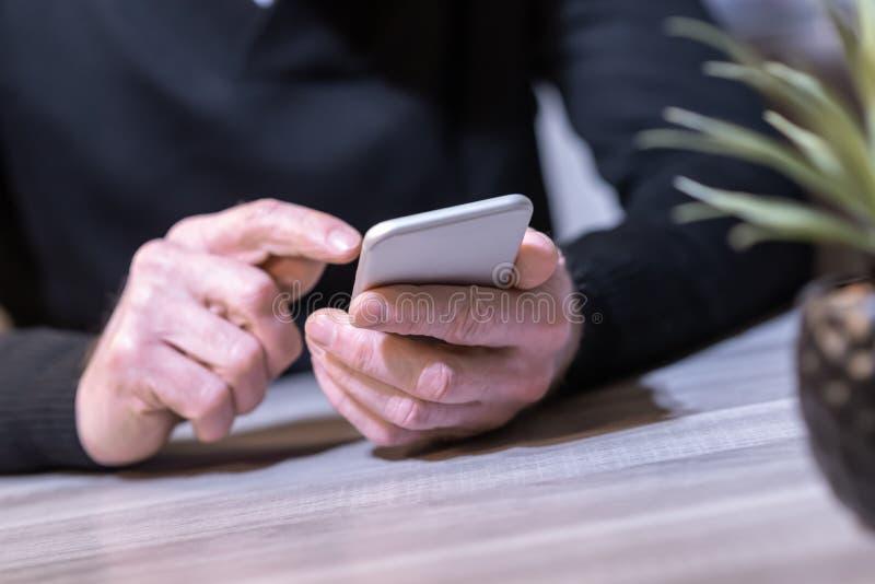 Рука используя мобильный телефон стоковое фото