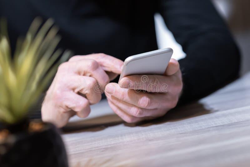 Рука используя мобильный телефон стоковые изображения