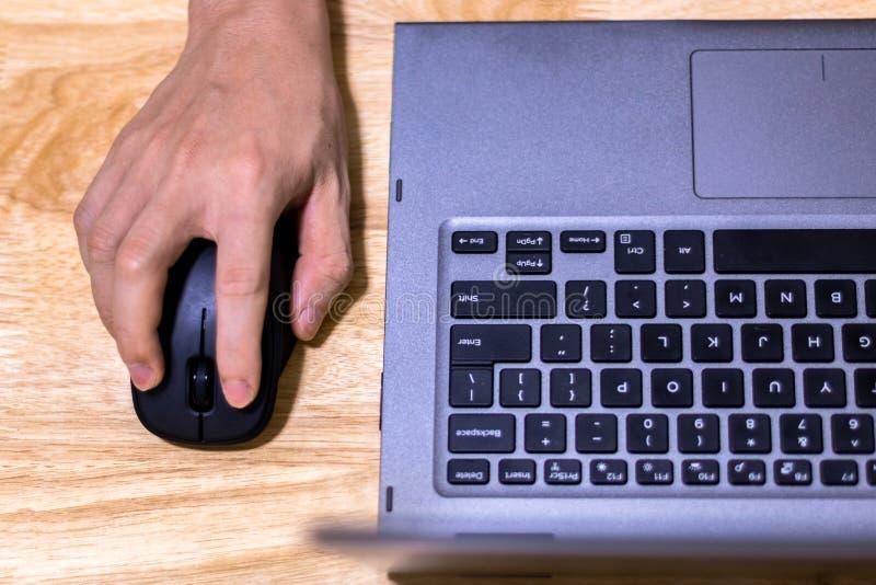 Рука используя мышь и ноутбук компьютера на столе стоковое фото