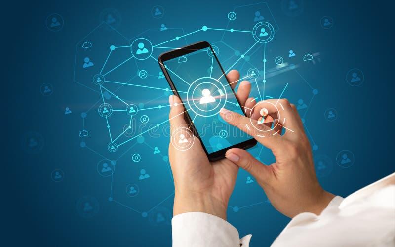 Рука используя smartphone для того чтобы соединить концепцию людей стоковые изображения rf