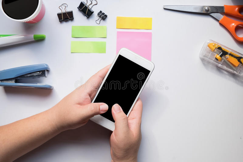 Рука используя smartphone на столе офиса стоковая фотография