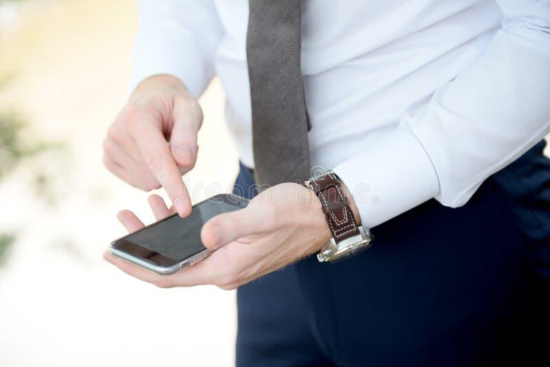 Рука используя мобильный телефон стоковое изображение