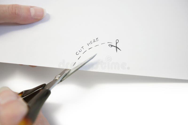 Рука используя ножницы для того чтобы отрезать бумагу стоковое фото rf