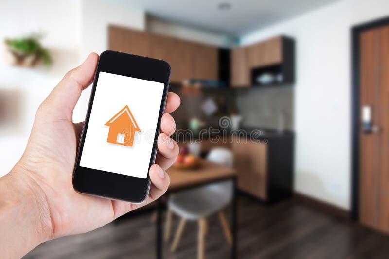 Рука используя smartphone домом app умным на черни стоковые изображения rf