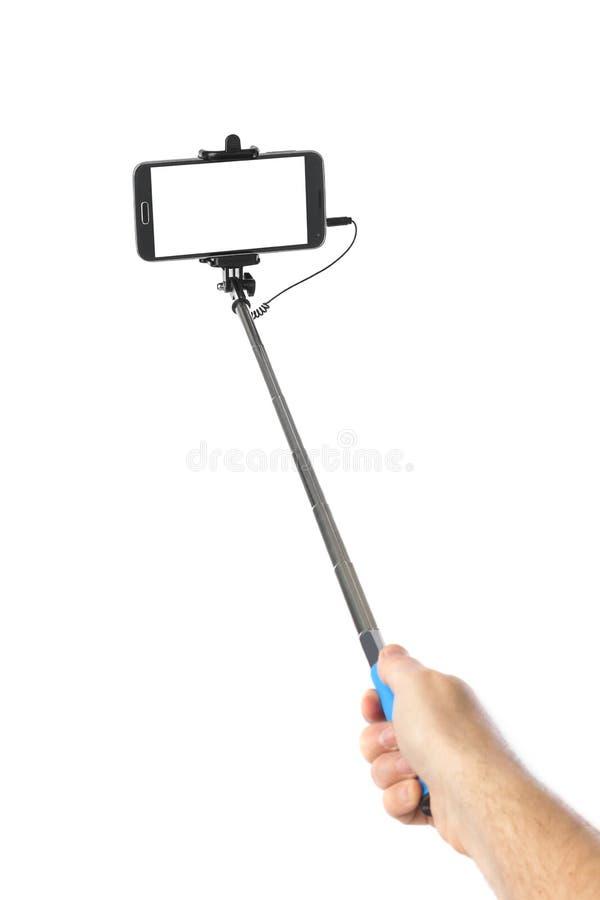 Рука и смартфон с ручкой selfie стоковое изображение
