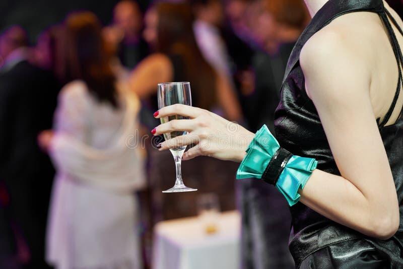 Рука и стекло гостя с вином на партии стоковая фотография rf