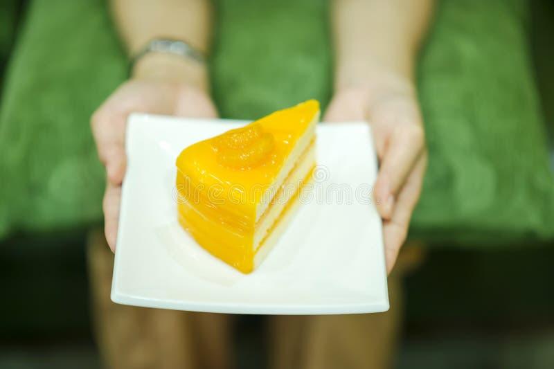 Рука и торт закусок десертов девушки очень вкусных lo здоровья стоковое фото