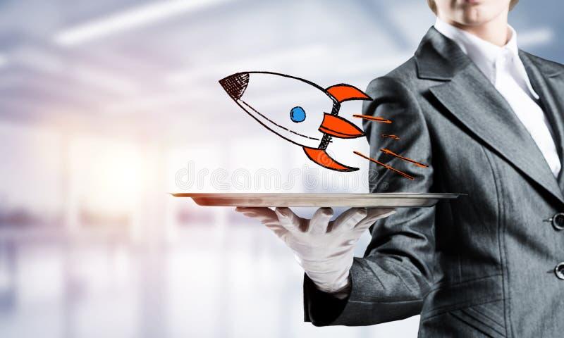 Рука кельнера представляя сделанную эскиз к ракету на подносе стоковое изображение