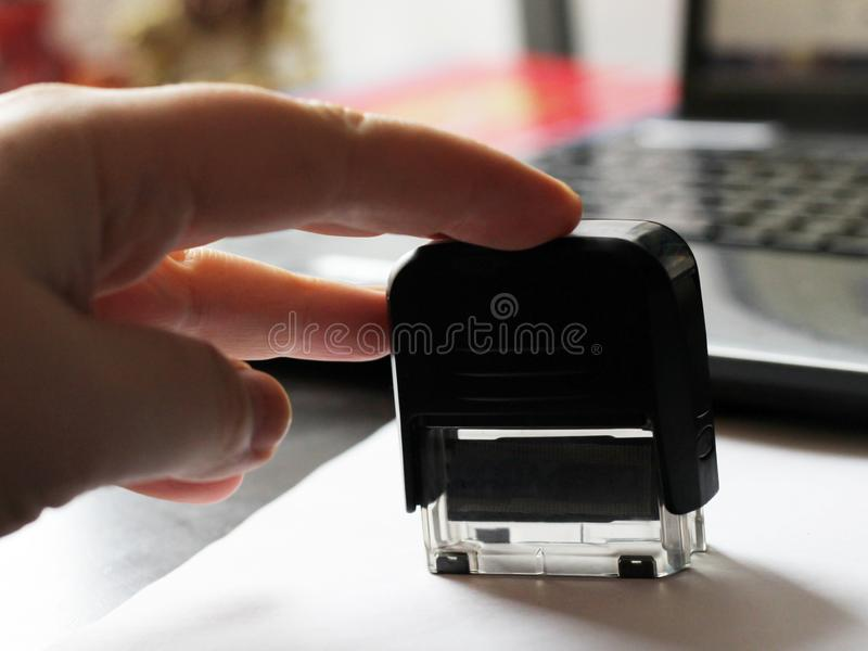 Рука кладет печать на документ стоковое изображение rf