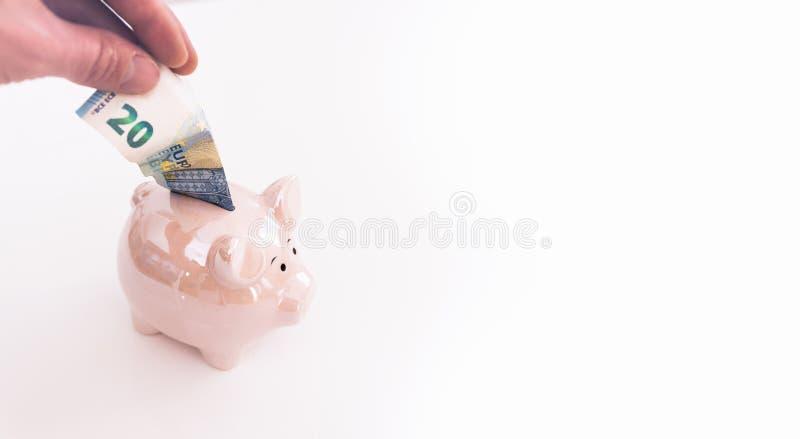 Рука кладя в евро 20 в копилку стоковое фото rf
