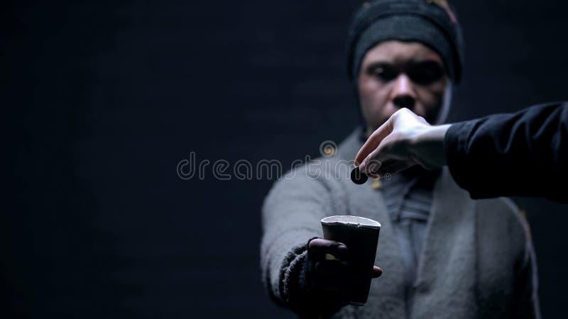 Рука кладя монетку в бумажный стаканчик попрошайки, социальной несправедливости, сострадания, доброты стоковые изображения rf