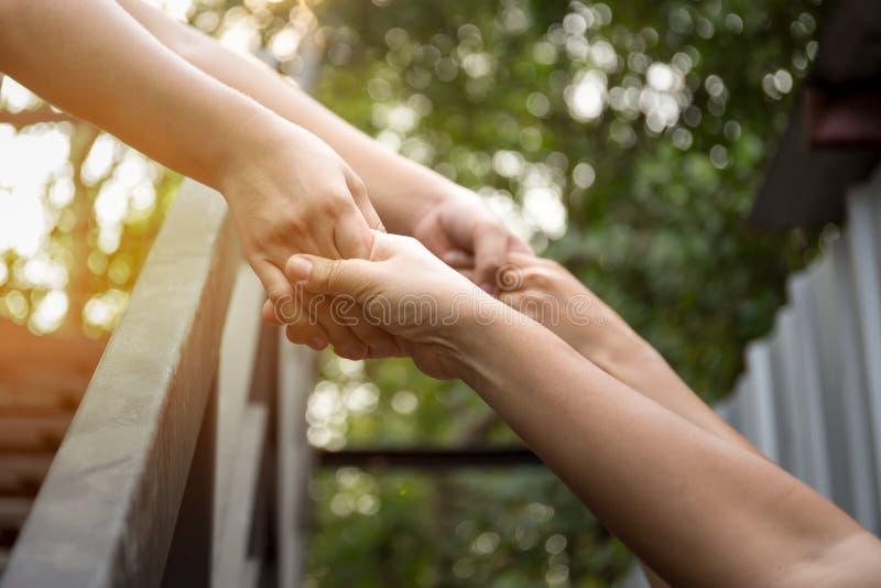 Рука концепции помощи достигая вне для помощи с светлым пирофакелом стоковая фотография rf