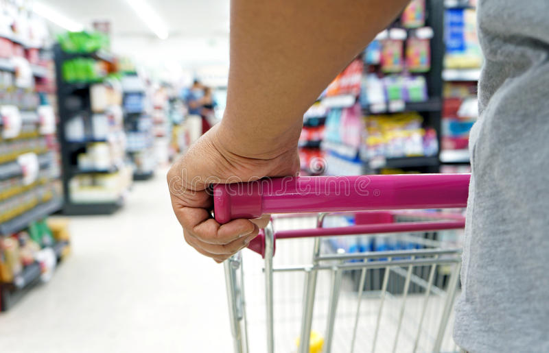 Рука крупного плана на магазинной тележкае стоковое фото rf