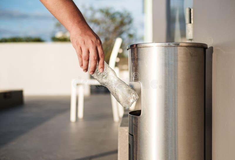 Рука кладя пластичный отход бутылки в погань отброса стоковое фото