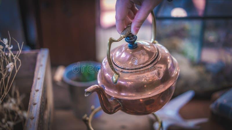 Рука лить горячий послеполуденный чай чайника стоковые изображения rf