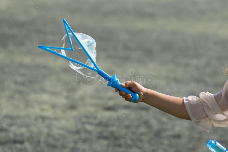 Рука маленькой маленькой девочки держа голубого создателя пузыря и делая пузыри стоковые фотографии rf