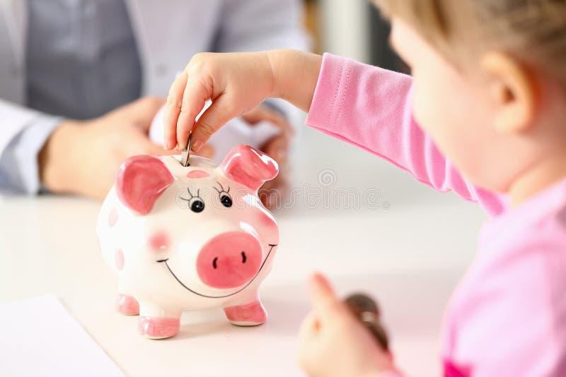 Рука маленькой девочки кладя монетки в смешной слот штыря копилки стоковая фотография