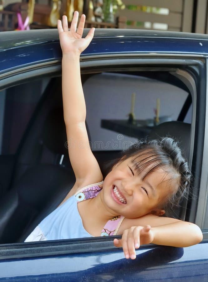Рука маленькой азиатской девушки развевая в автомобиле стоковые изображения rf