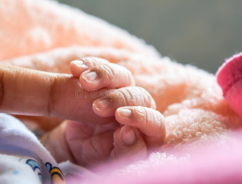 Рука младенца держа mother& x27; рука s на в первый раз после рождения которое симпатично и тепло стоковые изображения rf