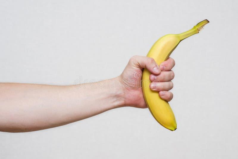 Рука молодого человека держа красивый, свежий, желтый банан Мужская рука держа банан стоковая фотография