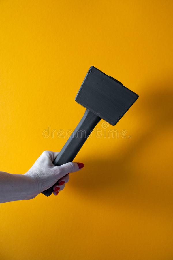 Рука молодой женщины держа черный деревянный молоток, ногти покрытые с красной политурой стоковое фото rf