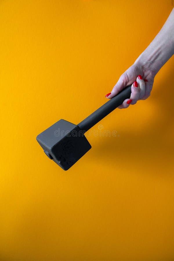 Рука молодой женщины держа черный деревянный молоток, ногти покрытые с красной политурой стоковые изображения rf