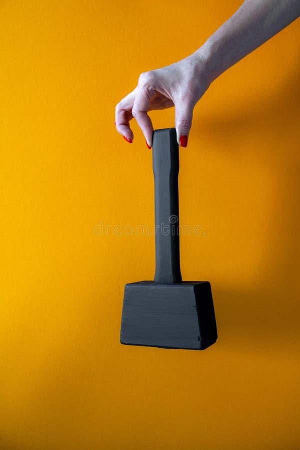 Рука молодой женщины держа черный деревянный молоток, ногти покрытые с красной политурой стоковое изображение