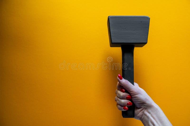 Рука молодой женщины держа черный деревянный молоток, ногти покрытые с красной политурой стоковое изображение rf