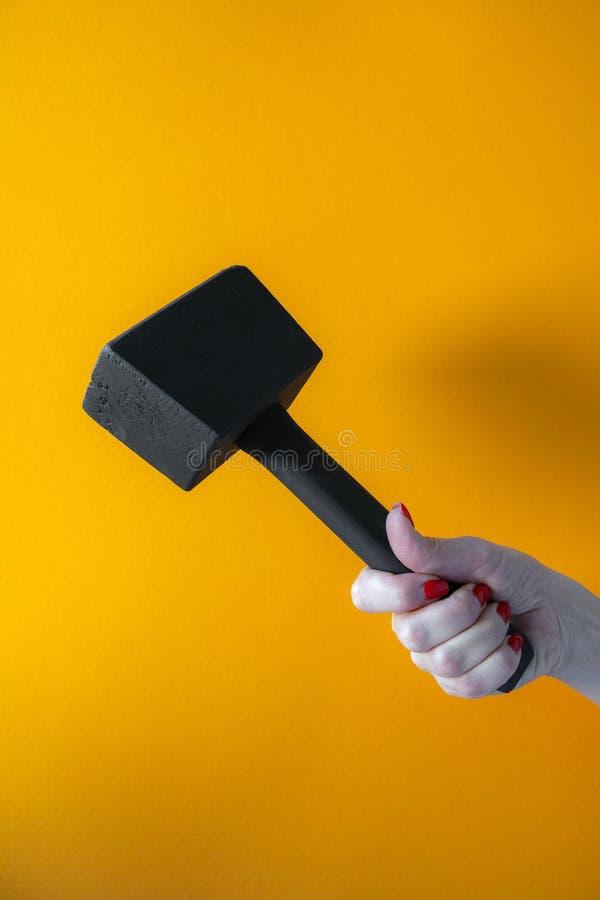 Рука молодой женщины держа черный деревянный молоток, ногти покрытые с красной политурой стоковые фото