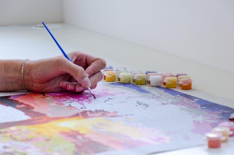 Рука молодой женщины красит щеткой изображение на таблице стоковое фото rf