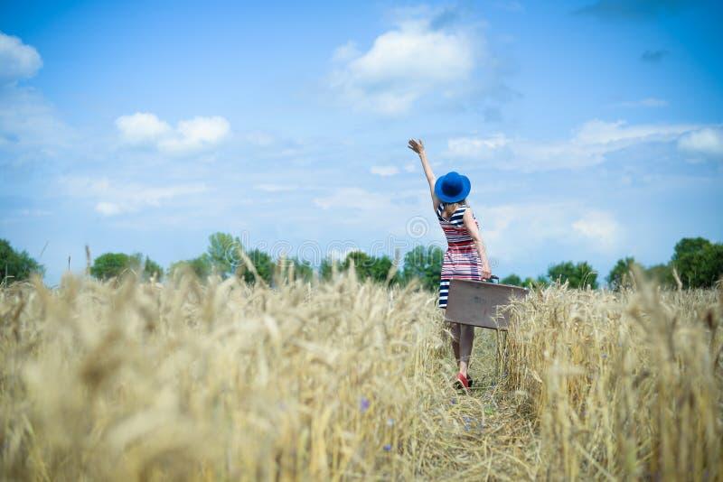 Рука молодой женщины развевая к небу на пшенице лета стоковая фотография rf
