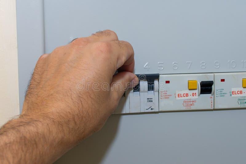 Рука нажимает выключатель в коробке взрывателя в жилом доме смотря электрические выключатели фиксируя потерю силы стоковое изображение rf