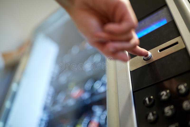 Рука нажимая кнопка на торговом автомате стоковые изображения