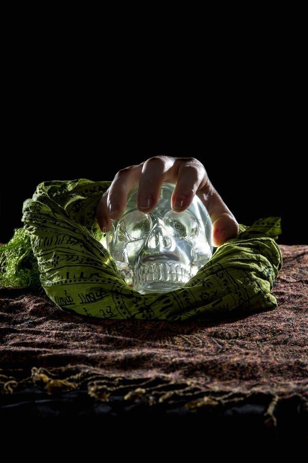 Рука на кристаллическом черепе стоковое фото rf